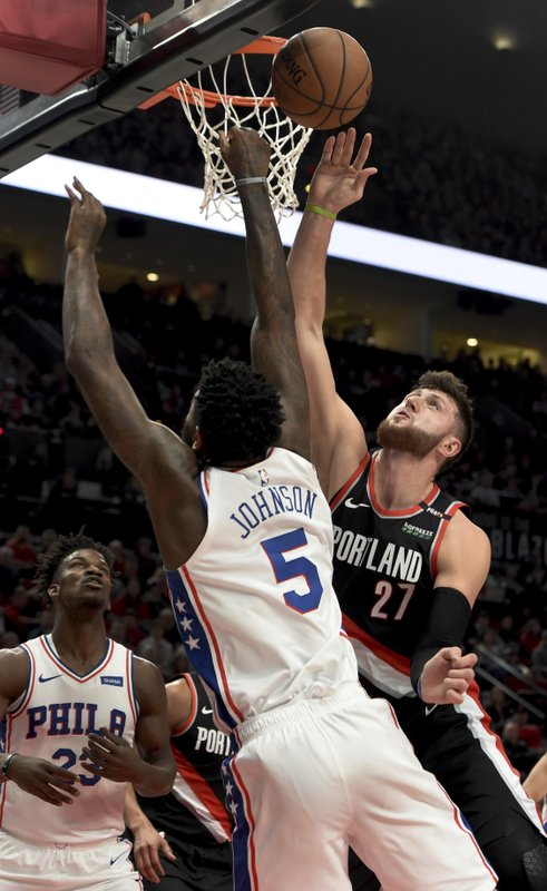 Portland Trail Blazers center Jusuf Nurkic, right, blocks the shot of Philadelphia 76ers center Amir Johnson, left, during the first half of an NBA basketball game in Portland, Ore. (AP Photo/Steve Dykes)