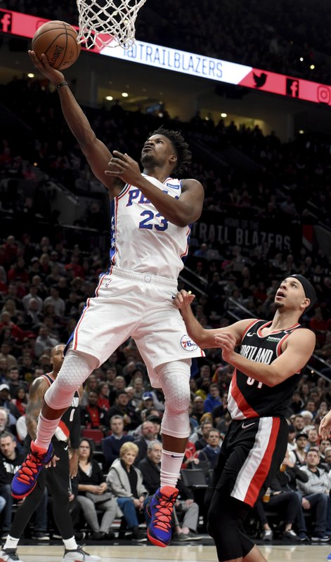 Philadelphia 76ers guard Jimmy Butler, left, drives to the basket on Portland Trail Blazers guard Seth Curry, right, during the first half of an NBA basketball game in Portland, Ore. (AP Photo/Steve Dykes)