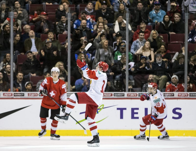 Russia's Pavel Shen, center, and Stepan Starkov, right, celebrate Shen's goal as Switzerland's Yannick Bruschweiler, left, watches during the third period of a world junior hockey championships game in Vancouver, British Columbia, Sunday, Dec. (Darryl Dyck/The Canadian Press via AP)