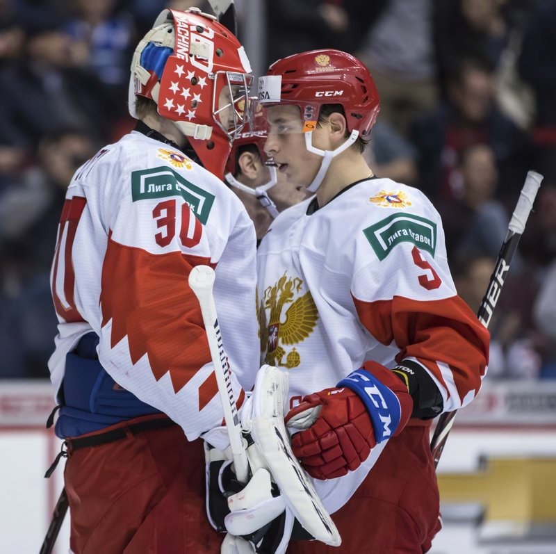 Russia goalie Danil Tarasov, left, and Artyom Galimov celebrate after Russia defeated Switzerland after a world junior hockey championships game in Vancouver, British Columbia, Sunday, Dec. (Darryl Dyck/The Canadian Press via AP)