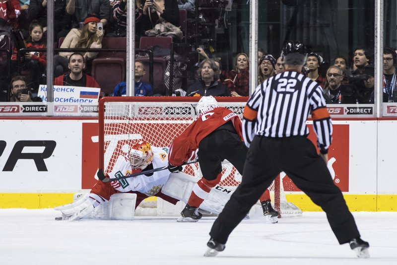 Russia goalie Danil Tarasov, back, stops Switzerland's Marco Lehmann on the first of two penalty shots awarded on the same play vie for the puck during the second period of a world junior hockey championships game in Vancouver, British Columbia, Sunday, Dec. (Darryl Dyck/The Canadian Press via AP)
