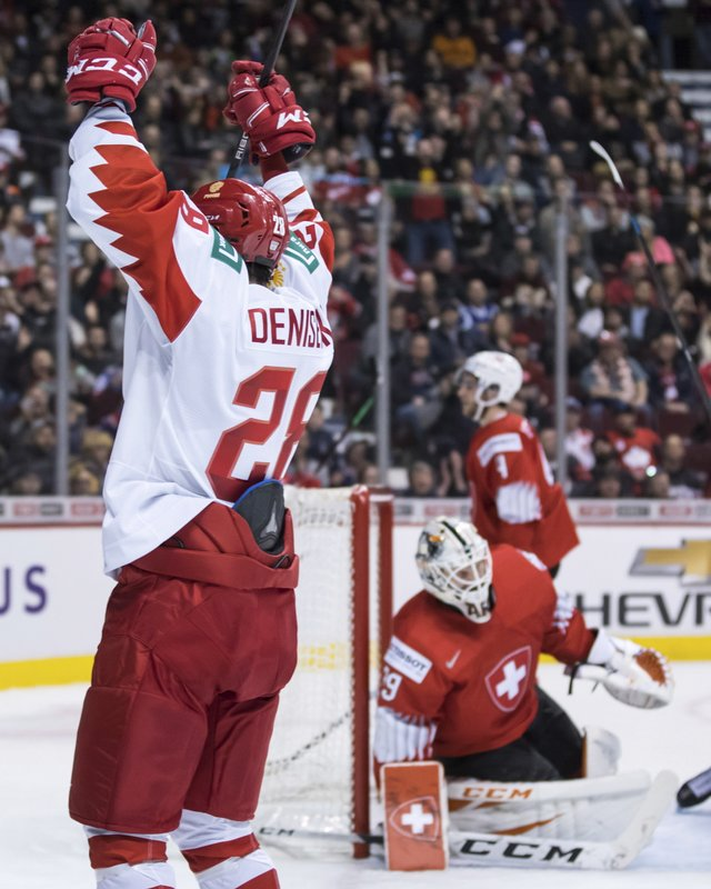 Russia's Grigori Denisenko, front left, celebrates his goal against Switzerland goalie Akira Schmid vie for the puck during the second period of a world junior hockey championships game in Vancouver, British Columbia, Sunday, Dec. (Darryl Dyck/The Canadian Press via AP)