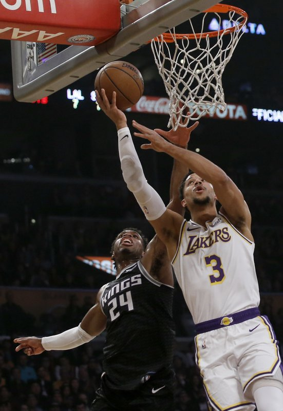 Los Angeles Lakers guard Josh Hart, right, shoots against Sacramento Kings guard Buddy Hield, left, during the first half of an NBA basketball game in Los Angeles, Sunday, Dec. (AP Photo/Alex Gallardo)