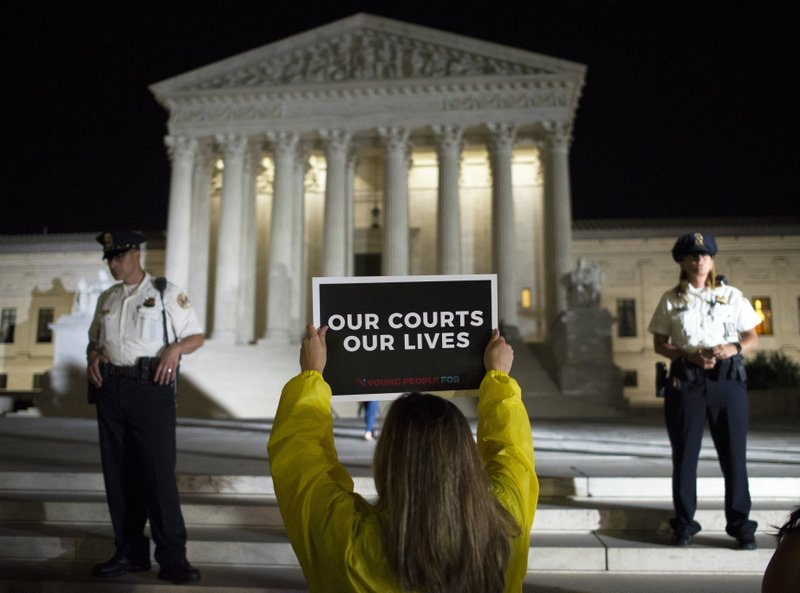 FILE - In this July 9, 2018, file photo a demonstrator protests in front of the Supreme Court in Washington. (AP Photo/Cliff Owen, File )