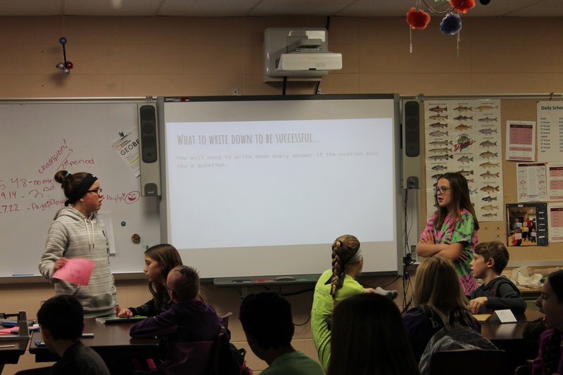 In this Tuesday, Dec. 18, 2018 photo, sixth-graders Malaya Naescher, standing, left, and Cami Lyons, standing, presented a science-based scavenger hunt for their classmates at Spearfish Middle School in Spearfish, S. (Kaija Swisher/Black Hills Pioneer via AP)