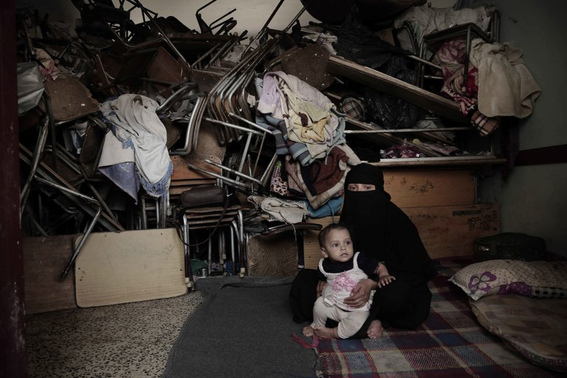 A woman sits with her baby inside a shelter for displaced persons in Ibb, Yemen, in this Aug. 3, 2018 photo. (AP Photo/Nariman El-Mofty)