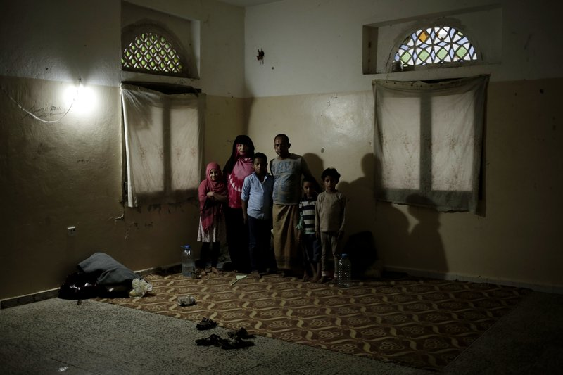 A family poses for a photograph in a shelter for displaced persons in Ibb, Yemen, in this Aug. 3, 2018, photo. (AP Photo/Nariman El-Mofty)