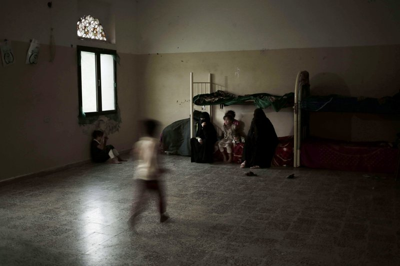 A family sits in their room at a shelter for displaced persons in Ibb, Yemen, in this Aug. 3, 2018, photo. (AP Photo/Nariman El-Mofty)