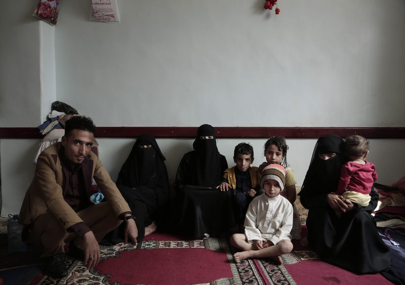 A family poses for a photograph in their room at a shelter for displaced persons in Ibb, Yemen, in this Aug. (AP Photo/Nariman El-Mofty)