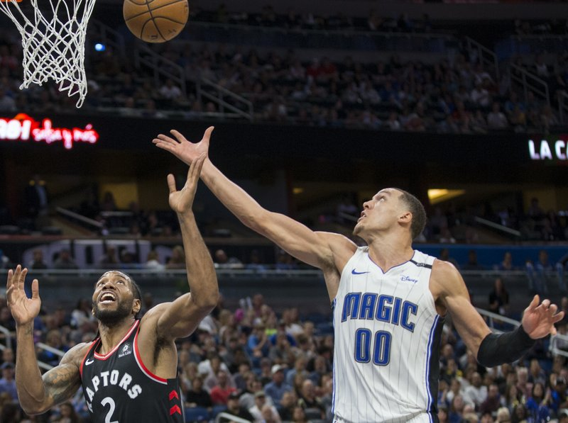 Toronto Raptors forward Kawhi Leonard (2) and Orlando Magic forward Aaron Gordon (00) go up for the rebound during the second half of an NBA basketball game in Orlando, Fla. (AP Photo/Willie J. Allen Jr.)