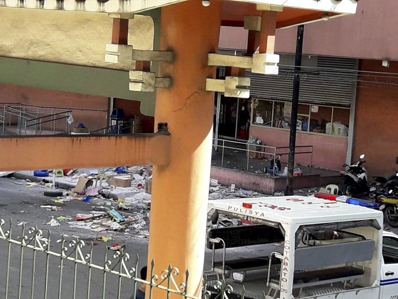 National Police investigators examine the site at the South Seas Mall following an explosion on New Year's Eve in Cotabato city, southern Philippines Monday, Dec. (AP Photo/Rainier Canoso)