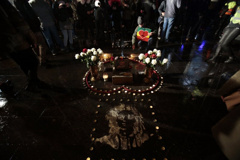 A man lights candles during a protest, in Banja Luka, Bosnia on Sunday, Dec. 30, 2018. Several thousand Bosnians have rallied in support of the man whose quest for the truth about his son's death has turned into a wider movement for justice and rule of law in the Balkan country. (AP Photo/Amel Emric)
