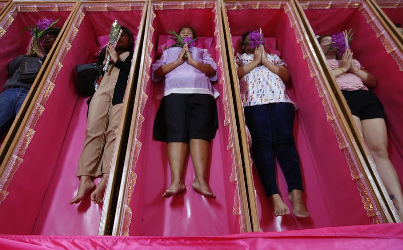 Worshippers pray as they take turns lying in coffins during a ceremony at the Takien temple in suburban Bangkok, Thailand Monday, Dec. (AP Photo/Sakchai lalit)