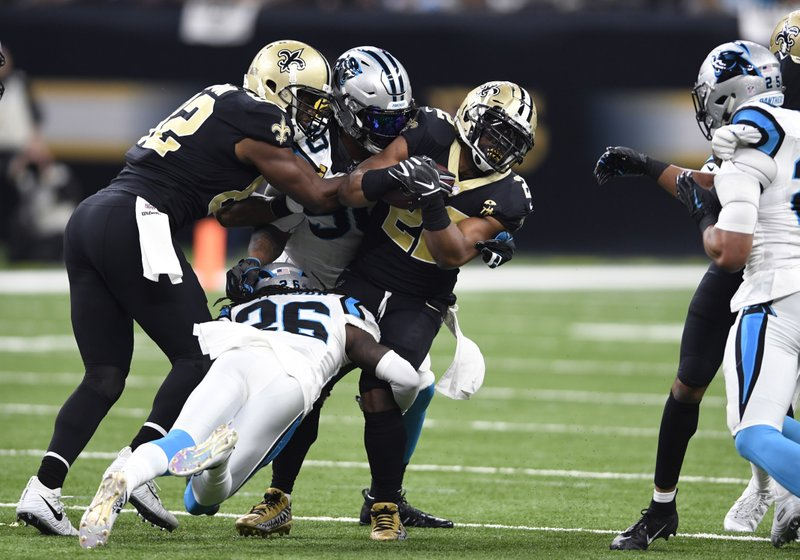 New Orleans Saints running back Mark Ingram (22) is tackled by Carolina Panthers cornerback Donte Jackson (26) and defensive end Julius Peppers (90), asSaints tight end Benjamin Watson (82) tries to protect the ball, in the first half of an NFL football game in New Orleans, Sunday, Dec. (AP Photo/Bill Feig)