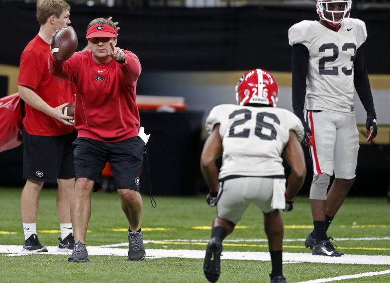 Georgia head coach Kirby Smart runs a drill as defensive back Tyrique McGhee (26) lines up at the Superdome in New Orleans, Friday, Dec. (AP Photo/Gerald Herbert)