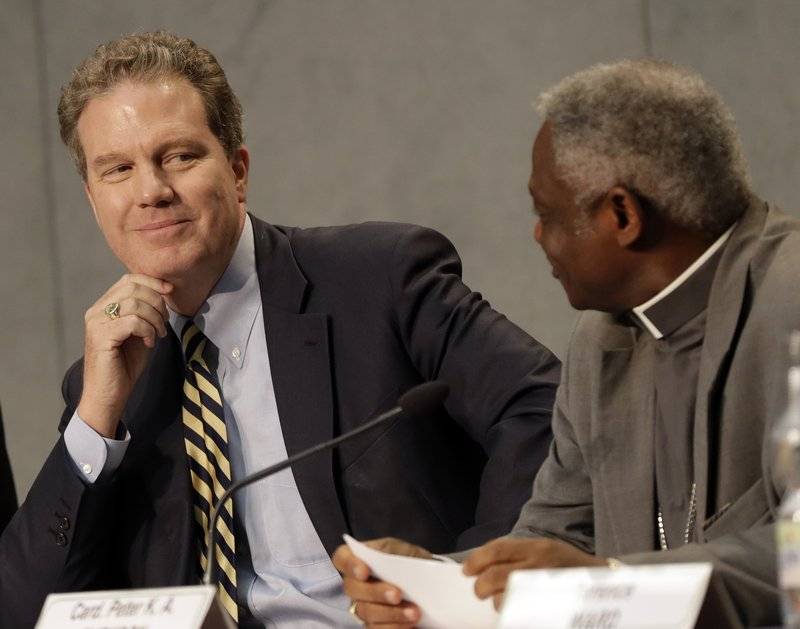 FILE - In this Thursday, Sept. 1, 2016 filer, Vatican spokesperson Greg Burke, left, smiles to Cardinal Peter Turkson during a press conference on the church's World Day of Prayer for the Care of Creation, at the Vatican. (AP Photo/Alessandra Tarantino, File)