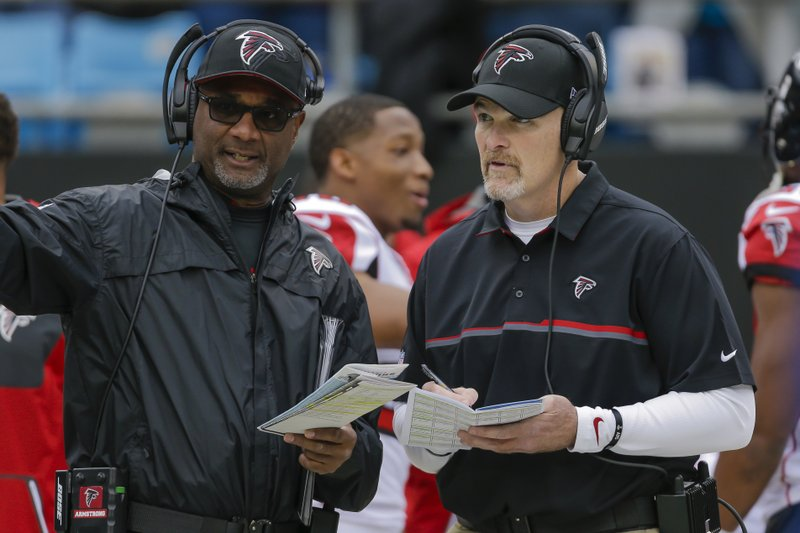 FILE - In this Dec. 24, 2016 file photo, Atlanta Falcons special teams coordinator Keith Armstrong, left, confers with head coach Dan Quinn before an NFL football game against the Carolina Panthers in Charlotte, N. (AP Photo/Bob Leverone, File)