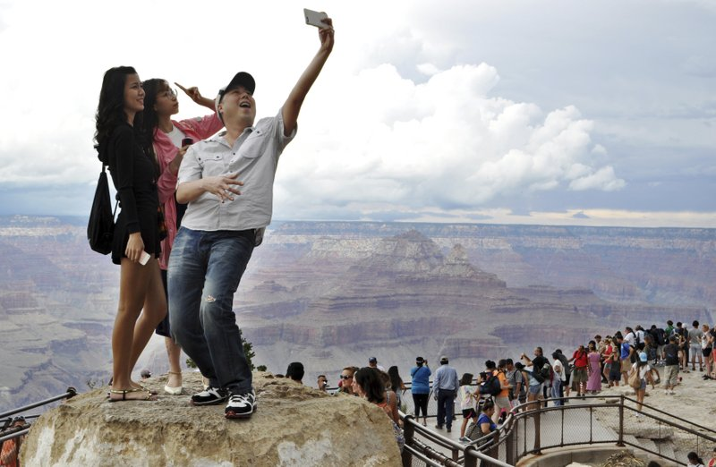 FILE - In this Aug. 2, 2015, file photo, tourists Joseph Lin, Ning Chao, center, and Linda Wang, left, pose for a selfie along the south rim at Grand Canyon National Park, Ariz. (Emery Cowan/Arizona Daily Sun via AP, File)