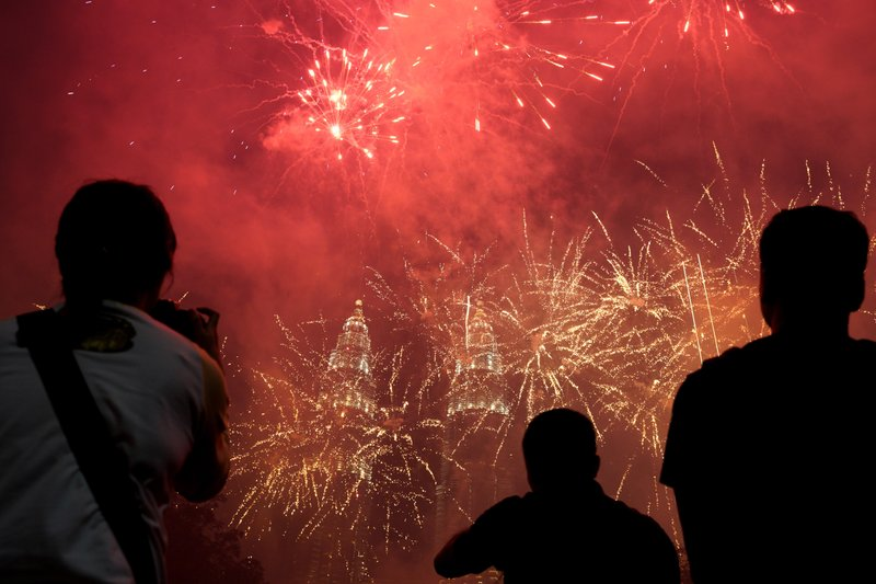 Spectators watch as fireworks explode in front of Malaysia's landmark building, the Petronas Twin Towers, during the New Year's celebration in Kuala Lumpur, Malaysia, Tuesday, Jan. (AP Photo/Yam G-Jun)