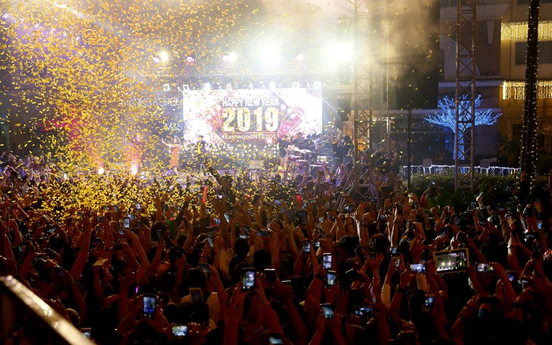 Confetti rains down on revelers at the Eastwood Shopping Mall as Filipinos welcome the New Year Tuesday, Jan. (AP Photo/Bullit Marquez)