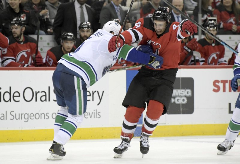 Vancouver Canucks defenseman Derrick Pouliot (5) checks New Jersey Devils left wing Miles Wood (44) during the second period of an NHL hockey game Monday, Dec. (AP Photo/Bill Kostroun)
