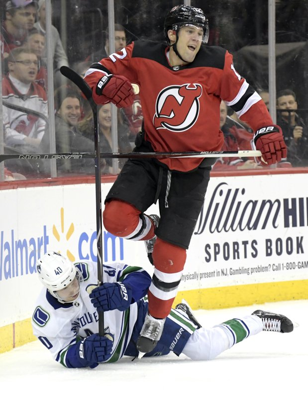 New Jersey Devils defenseman Ben Lovejoy (12) goes over Vancouver Canucks center Elias Pettersson (40) during the first period of an NHL hockey game Monday, Dec. (AP Photo/Bill Kostroun)