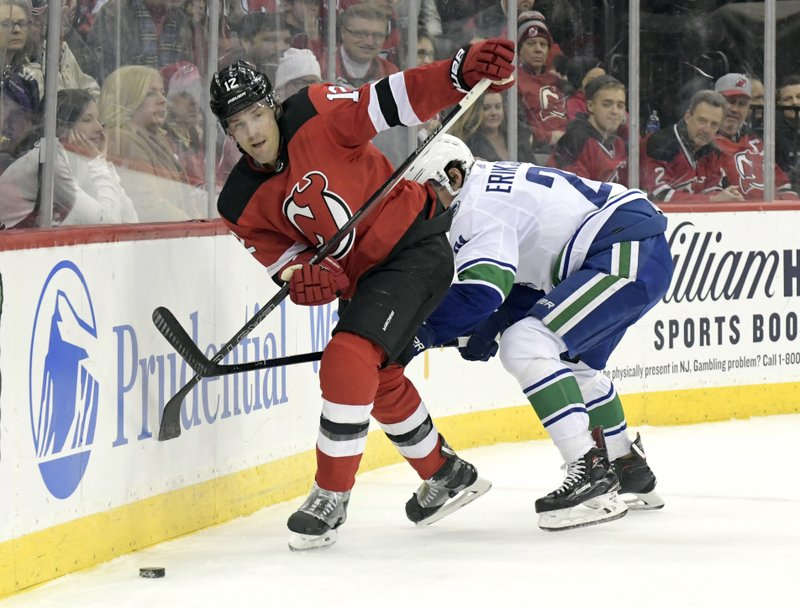 New Jersey Devils defenseman Ben Lovejoy (12) passes the puck as he is checked by Vancouver Canucks left wing Loui Eriksson (21) during the first period of an NHL hockey game Monday, Dec. (AP Photo/Bill Kostroun)