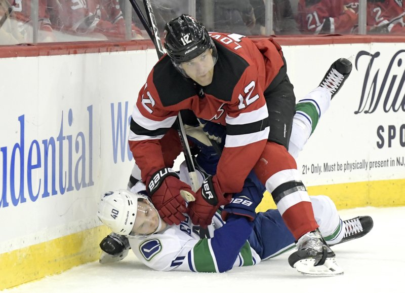 New Jersey Devils defenseman Ben Lovejoy (12) checks Vancouver Canucks center Elias Pettersson (40) during the first period of an NHL hockey game Monday, Dec. (AP Photo/Bill Kostroun)