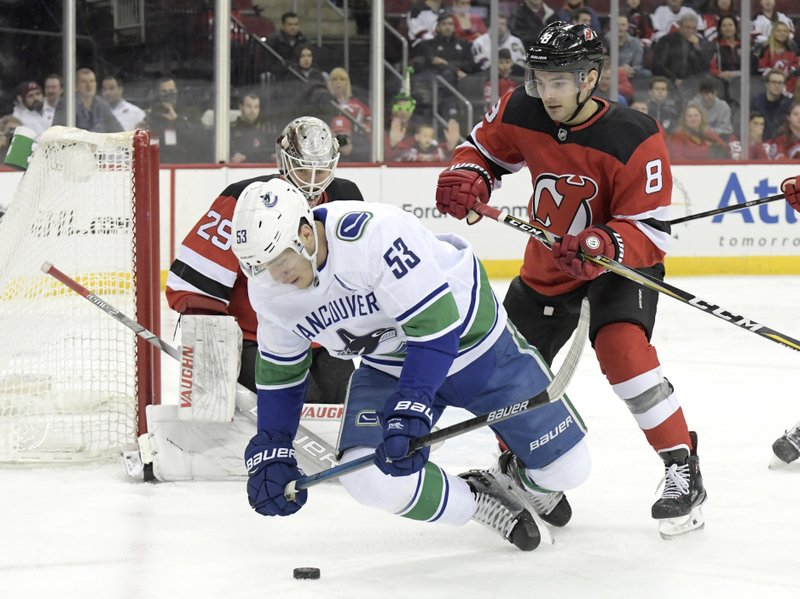 New Jersey Devils defenseman Will Butcher (8) checks Vancouver Canucks center Bo Horvat (53) as Devils goaltender Mackenzie Blackwood (29) looks on during the first period of an NHL hockey game Monday, Dec. (AP Photo/Bill Kostroun)