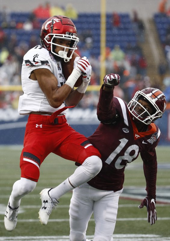 Cincinnati wide receiver Rashad Medaris, left, catches a pass in front of Virginia Tech defensive back Tyree Rodgers in the first half of the Military Bowl NCAA college football game, Monday, Dec. (AP Photo/Patrick Semansky)