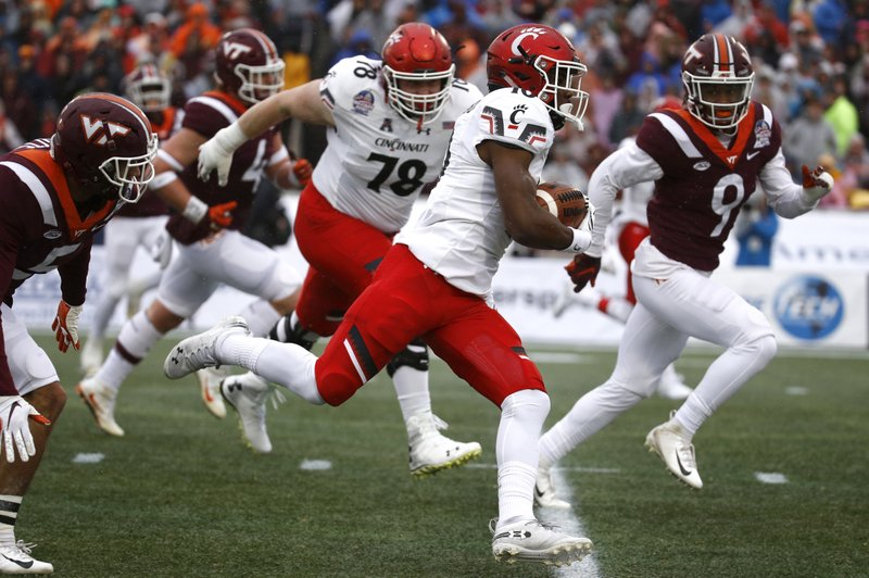 Cincinnati running back Charles McClelland, center, rushes for a touchdown in the first half of the Military Bowl NCAA college football game against Virginia Tech, Monday, Dec. (AP Photo/Patrick Semansky)