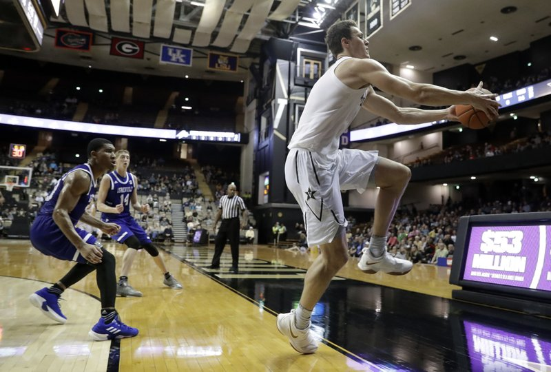 Vanderbilt forward Yanni Wetzell, right, saves the ball from going out of bounds in the second half of an NCAA college basketball game against UNC Asheville, Monday, Dec. (AP Photo/Mark Humphrey)