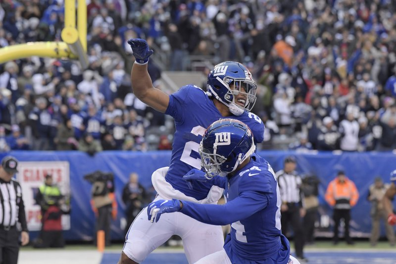 New York Giants' Saquon Barkley, top, celebrates his touchdown with teammates during the second half of an NFL football game against the Dallas Cowboys, Sunday, Dec. (AP Photo/Bill Kostroun)