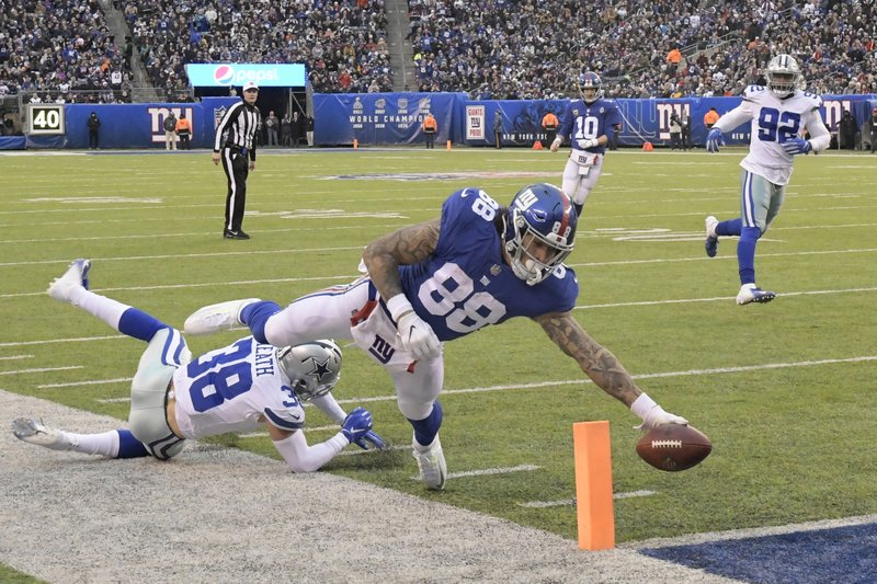 New York Giants' Evan Engram, right, scores a touchdown during the second half of an NFL football game against the Dallas Cowboys, Sunday, Dec. (AP Photo/Bill Kostroun)
