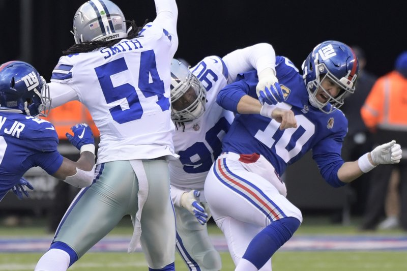 New York Giants quarterback Eli Manning, right, is hit by Dallas Cowboys' Demarcus Lawrence during the first half of an NFL football game, Sunday, Dec. (AP Photo/Bill Kostroun)
