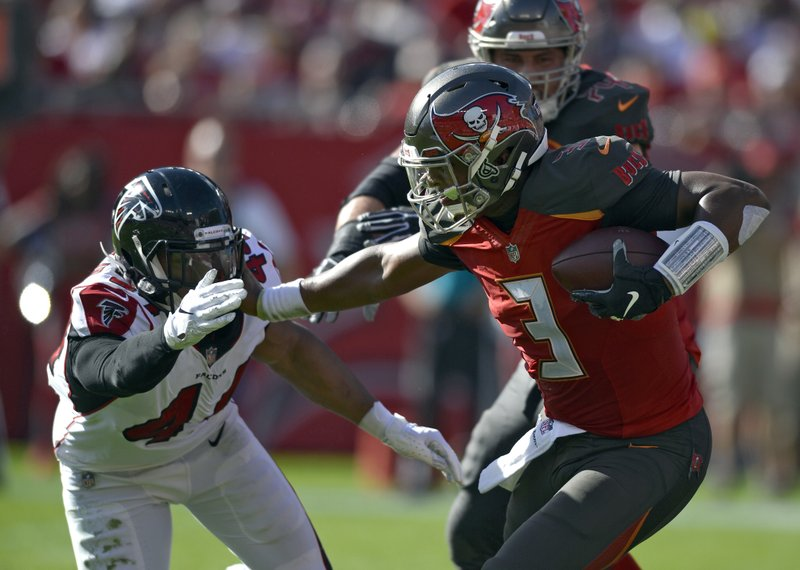 Tampa Bay Buccaneers quarterback Jameis Winston (3) stiff arms Atlanta Falcons defensive end Vic Beasley (44) on a run during the first half of an NFL football game Sunday, Dec. (AP Photo/Jason Behnken)