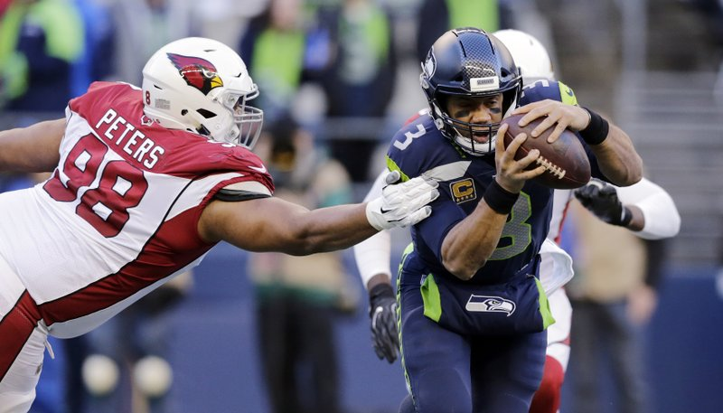 Seattle Seahawks quarterback Russell Wilson, right, tries to scramble away from Arizona Cardinals' Corey Peters during the second half of an NFL football game, Sunday, Dec. (AP Photo/John Froschauer)