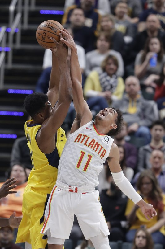 Indiana Pacers' Thaddeus Young, left, and Atlanta Hawks' Trae Young (11) battle for a rebound during the first half of an NBA basketball game, Monday, Dec. (AP Photo/Darron Cummings)