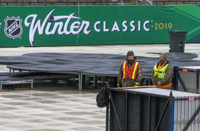 In this Dec. 21, 2018, photo, crews work to set up a hockey rink and staging for the NHL Winter Classic hockey game between the Chicago Blackhawks and the Boston Bruins at Notre Dame Stadium in South Bend, Ind. (Robert Franklin/South Bend Tribune via AP)