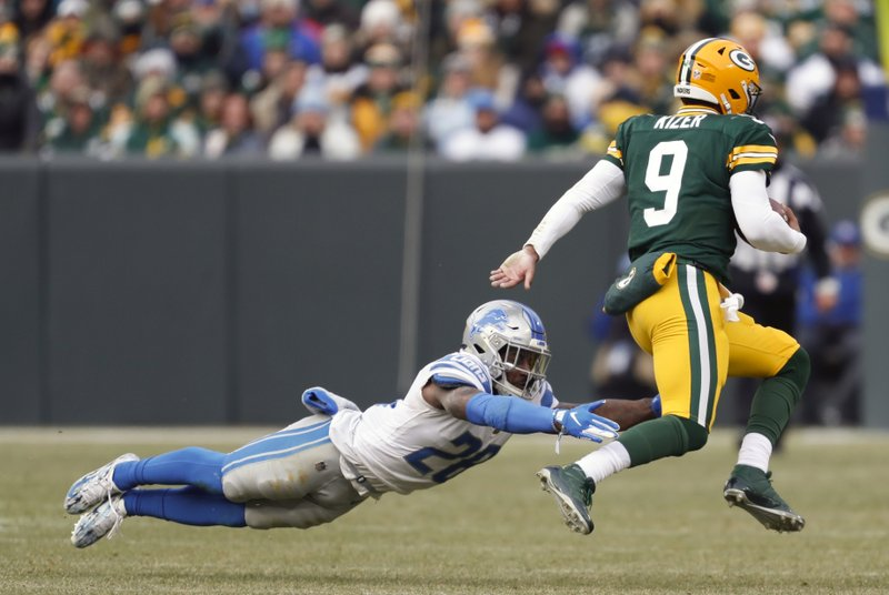 Green Bay Packers' DeShone Kizer (9) runs for a first down past Detroit Lions' Quandre Diggs during the second half of an NFL football game Sunday, Dec. (AP Photo/Matt Ludtke)