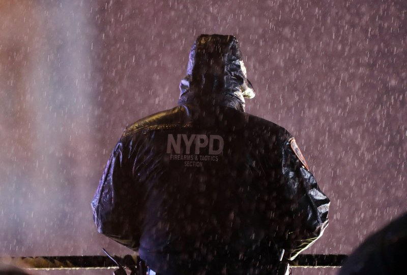 A member of the New York Police Department watches over revelers as they wait for midnight during the New Year's Eve celebration in New York's Times Square, Monday, Dec. (AP Photo/Frank Franklin II)