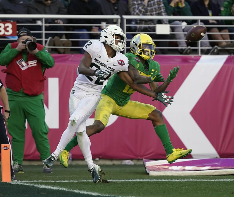Oregon wide receiver Dillon Mitchell, right, catches a touchdown pass in front of Michigan State cornerback Josiah Scott (22) during the second half of the Redbox Bowl NCAA college football game Monday, Dec. (AP Photo/Tony Avelar)