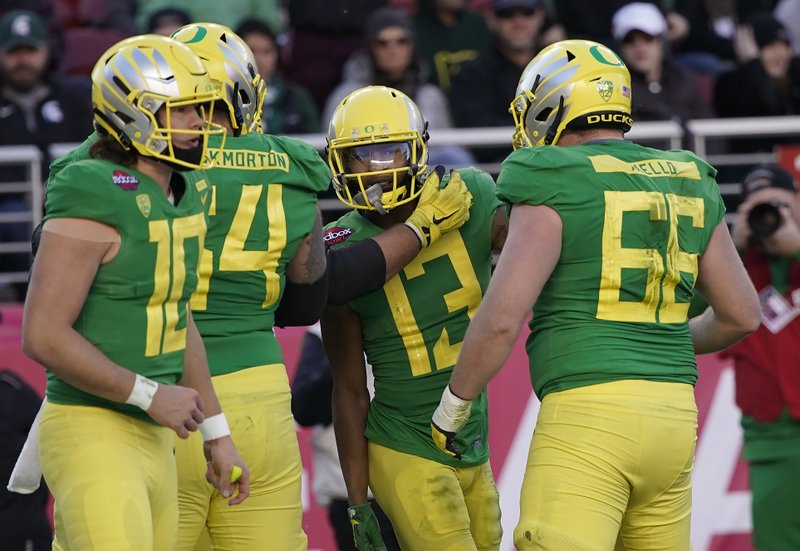 Oregon wide receiver Dillon Mitchell (13) celebrates with Brady Aiello (66) and Calvin Throckmorton (54) after scoring a touchdown against Michigan State during the second half of the Redbox Bowl NCAA college football game Monday, Dec. (AP Photo/Tony Avelar)