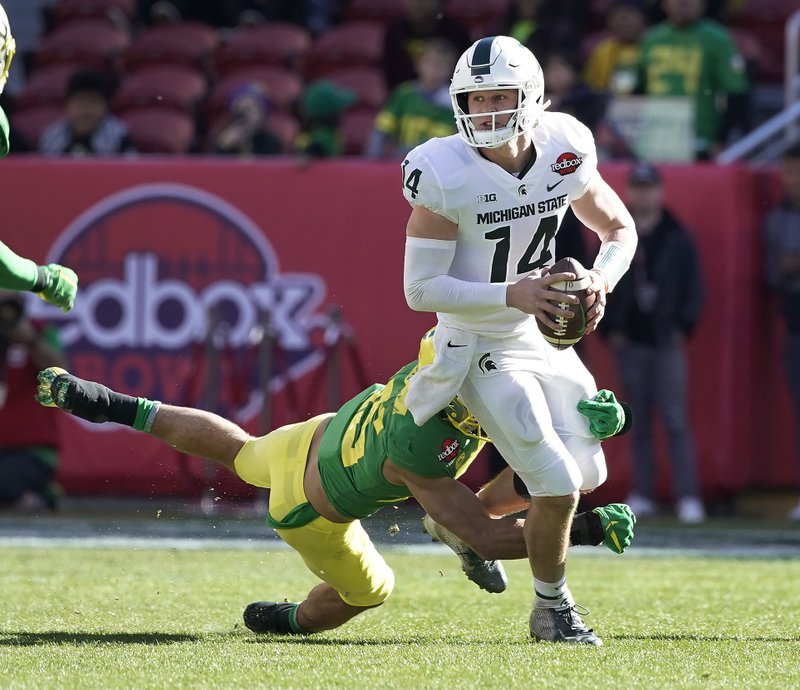 Michigan State quarterback Brian Lewerke (14) is sacked by Oregon safety Brady Breeze (25) during the first half of the Redbox Bowl NCAA college football game Monday, Dec. (AP Photo/Tony Avelar)