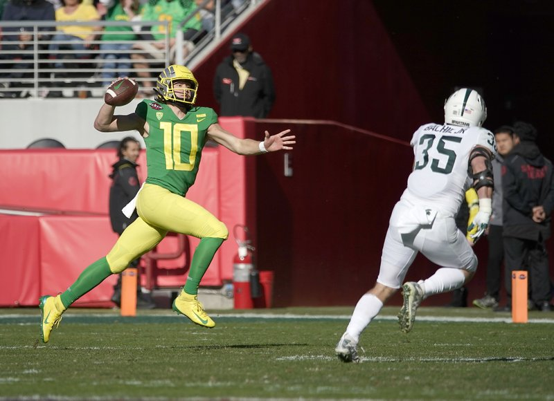 Oregon quarterback Justin Herbert (10) scrabbles for a first down against Michigan State linebacker Joe Bachie (35) during the first half of the Redbox Bowl NCAA college football game Monday, Dec. (AP Photo/Tony Avelar)