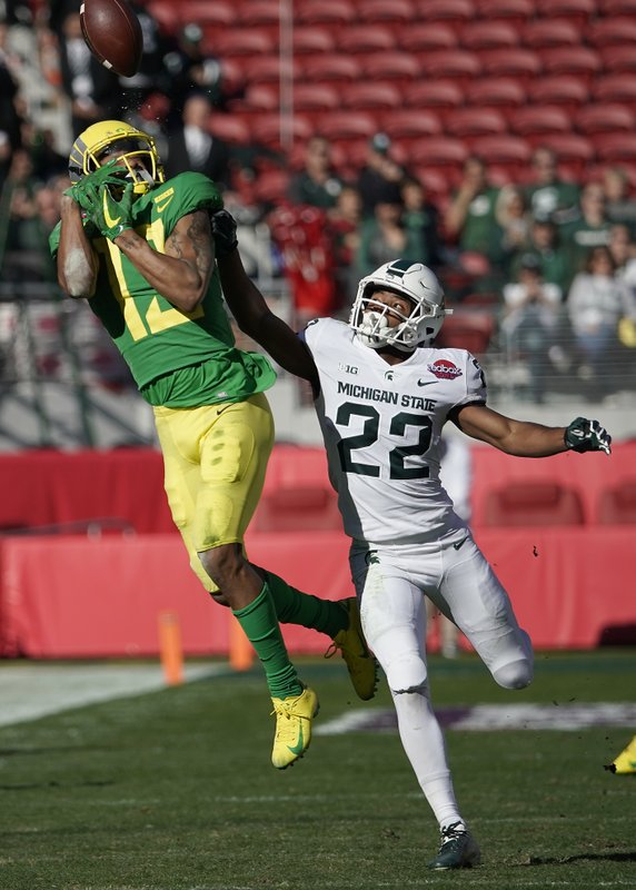 Oregon wide receiver Dillon Mitchell (13) cannot make a catch against Michigan State cornerback Josiah Scott (22) during the first half of the Redbox Bowl NCAA college football game Monday, Dec. (AP Photo/Tony Avelar)