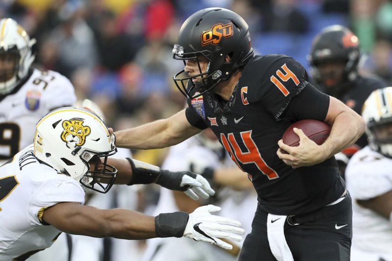 Oklahoma State quarterback Taylor Cornelius tries to stiff-arm Missouri linebacker Terez Hall during the first half of the Liberty Bowl NCAA college football game in Memphis, Tenn. (Joe Rondone/The Commercial Appeal via AP)