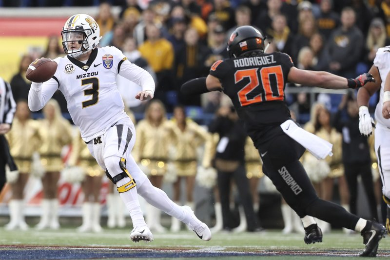 Missouri quarterback Drew Lock tries to escape the pocket as Oklahoma State safety Malcolm Rodriguez pursues during the first half of the Liberty Bowl NCAA college football game in Memphis, Tenn. (Joe Rondone/The Commercial Appeal via AP)