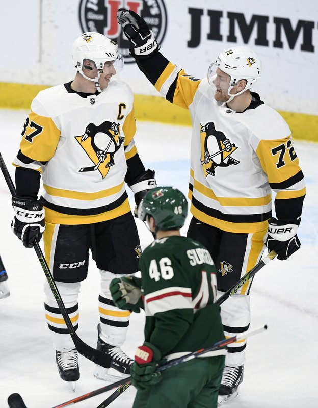 Minnesota Wild's Jared Spurgeon (46) watches as Pittsburgh Penguins' Sidney Crosby (87) and Patric Hornqvist (72), of Sweden, celebrate a power-play goal by Crosby during the first period of an NHL hockey game Monday, Dec. (AP Photo/Hannah Foslien)