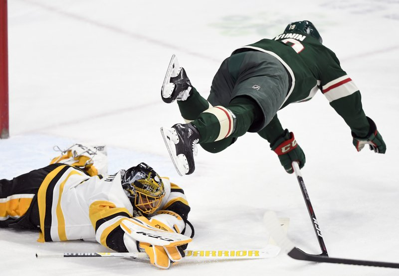 Pittsburgh Penguins goaltender Casey DeSmith (1) covers the puck as Minnesota Wild center Luke Kunin (19) jumps over him during the first period of an NHL hockey game Monday, Dec. (AP Photo/Hannah Foslien)